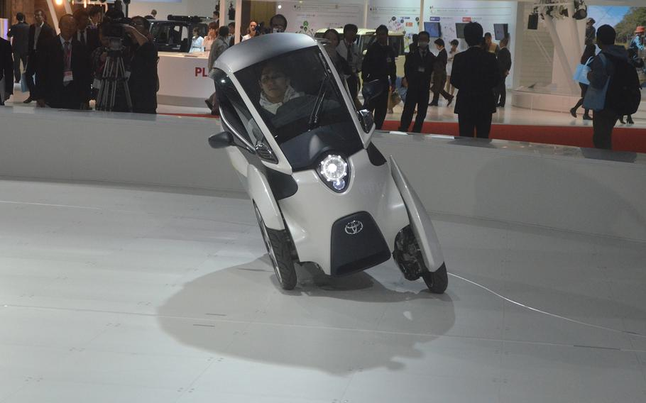 A driver takes a spin in a Toyota 3-wheel electric concept car.