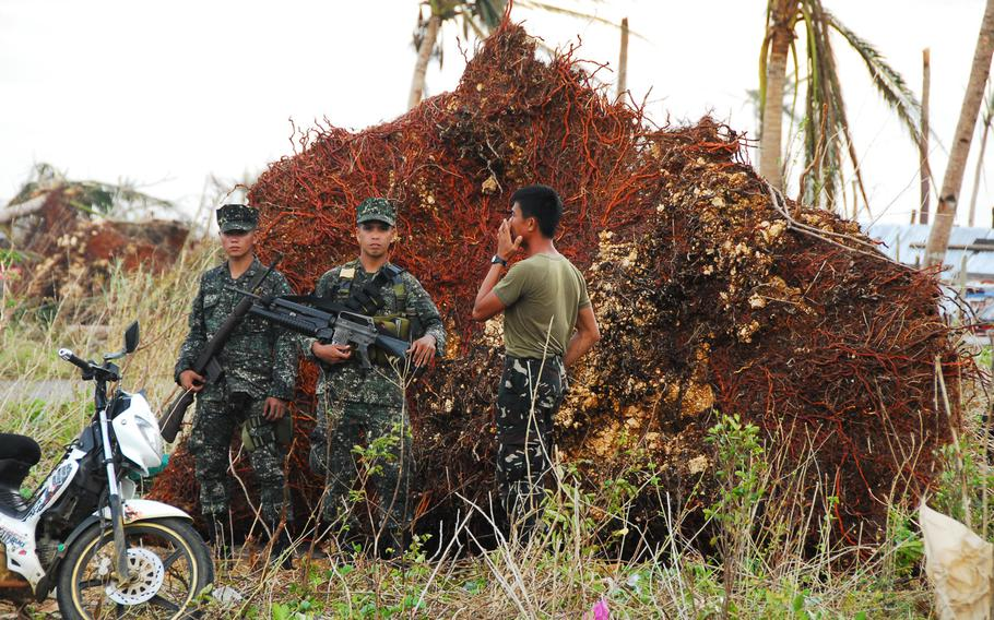 Filipino troops stand guard in front of a fallen coconut tree on Nov. 21, 2013. They took over responsibility for security at Guiuan Airport from U.S. Marines this week.