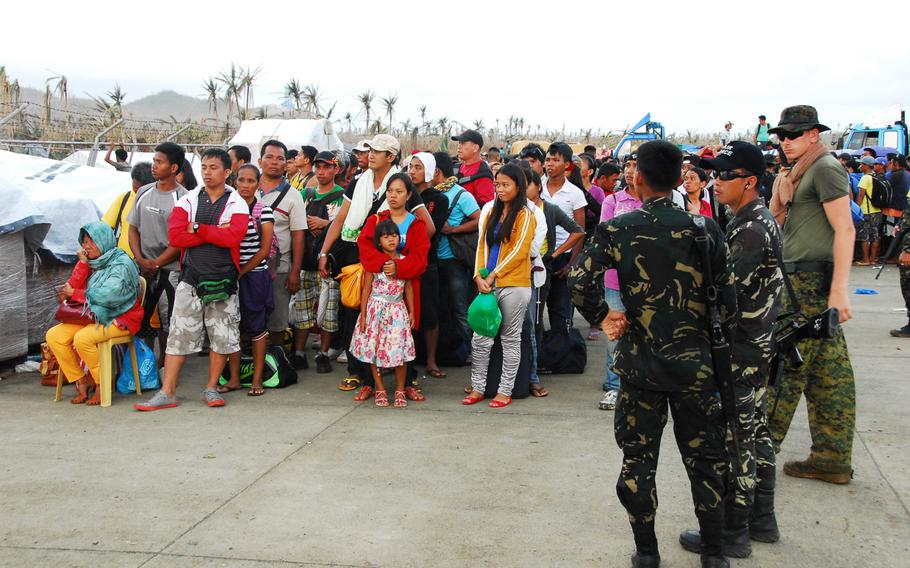 Filipino troops and a U.S. Marine watch over people waiting for evacuation from Guiuan on Nov. 22, 2013. The Filipinos took over responsibility for security at Guiuan Airport from U.S. Marines this week. After more than a week on the ground helping Typhoon Haiyan victims, the Marines are packing up and heading back to Okinawa.
