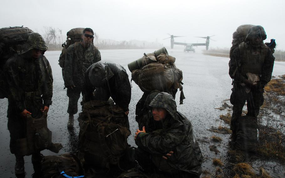 U.S. Marines wait in the rain at the Guiuan airport in the Philippines on Nov. 22, 2013. After more than a week on the ground helping Typhoon Haiyan victims, the Marines are packing up and heading back to Okinawa.