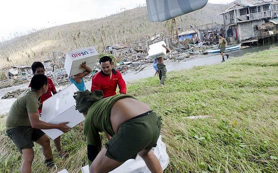 Filipinos unload boxes of relief supplies from a V-22 Osprey at a typhoon-ravaged village last week.