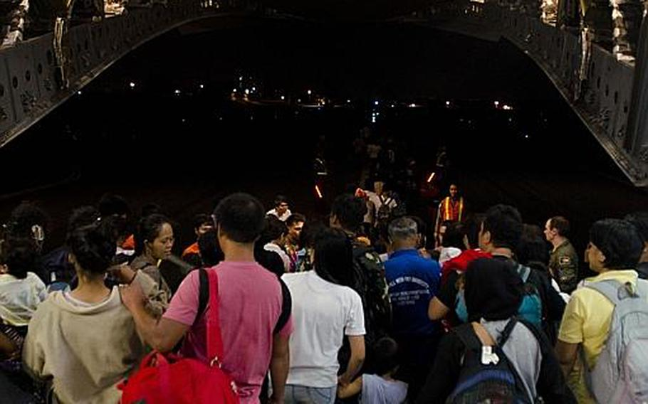 A team of relief workers from multiple nations welcome nearly 500 victims of Super Typhoon Haiyan to Villamore Airbase in Manila, Philippines after they were evacuated from Tacloban Airport, Tacloban, Philippines on Nov. 22, 2013.