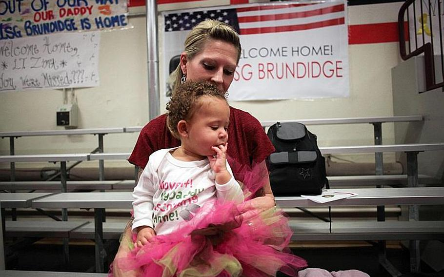 Staff Sgt. Amy Brundidge holds her one-year-old daughter Kiara Saturday, Nov. 23, as they wait for the arrival of the 39th Transportation Battalion (Movement Control) and her husband Master Sgt. Ronald Brudidge from a nine-month deployment to Afghanistan.