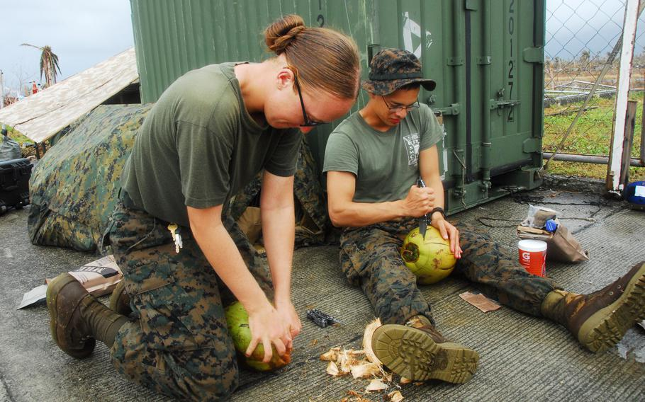 Marine Cpl. Kaycee Morales, 22, of Las Cruces, N.M., left, and Navy Hospital Corpsman 3 Israel Nolen, 20 of El Paso, Texas, work to crack open coconuts during typhoon relief operations in The Philippines on Friday, Nov. 22, 2013.
