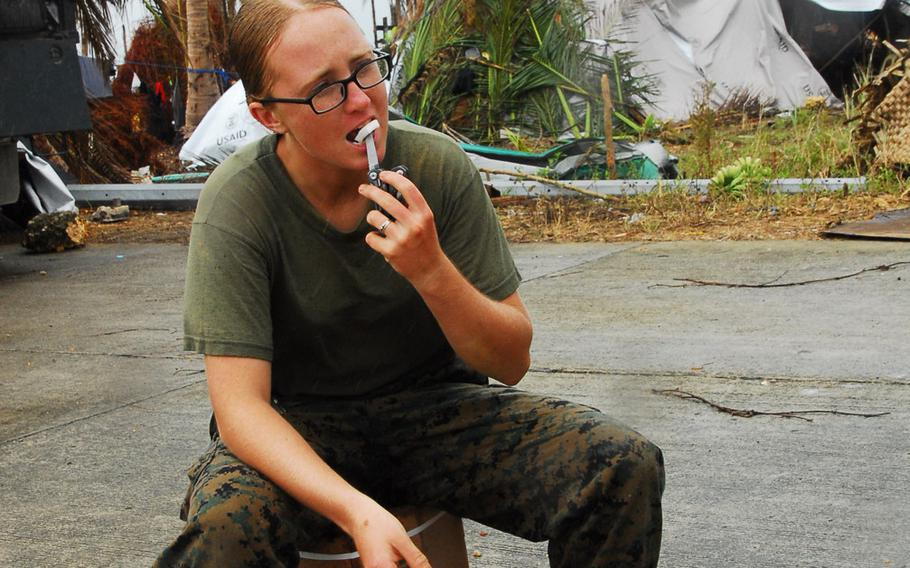 Marine Cpl. Kaycee Morales, 22, of Las Cruces, N.M., eats a coconut during typhoon relief operations in The Philippines on Friday, Nov. 22, 2013.