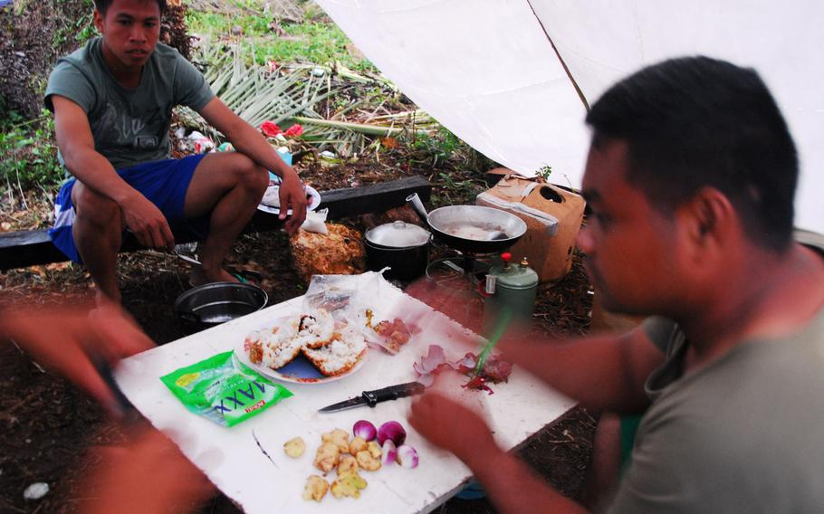 Filipino airmen prepare pork adobo during typhoon relief operations in The Philippines on Thursday, Nov. 21, 2013.