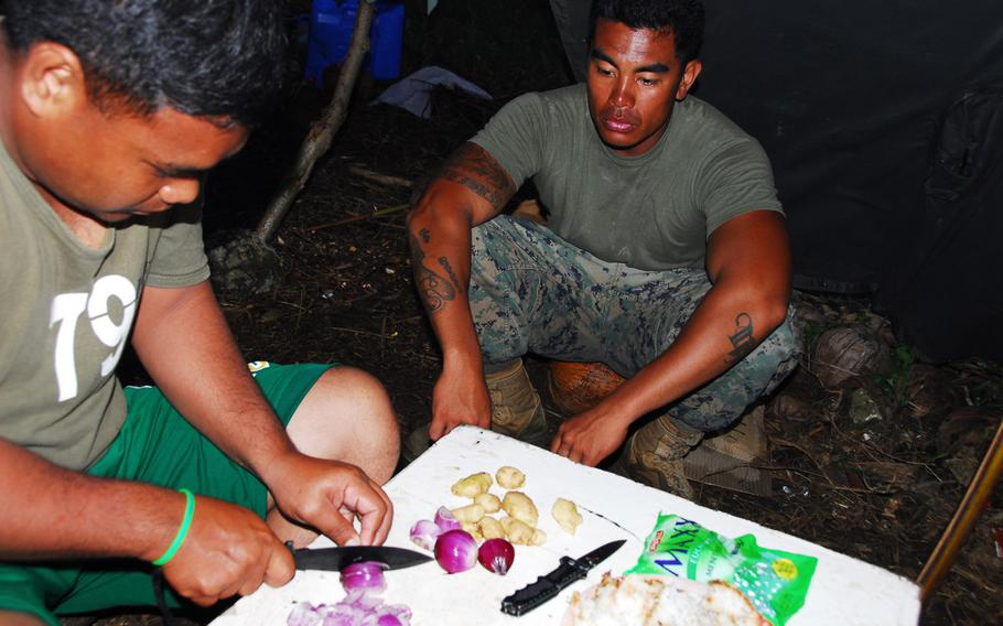 A Filipino airman prepares a meal to share with U.S. Marine Staff Sgt. John Suyat, 32, of Alexandria, Va., on Thursday, Nov. 21, 2013, during typhoon relief operations in the Philippines.