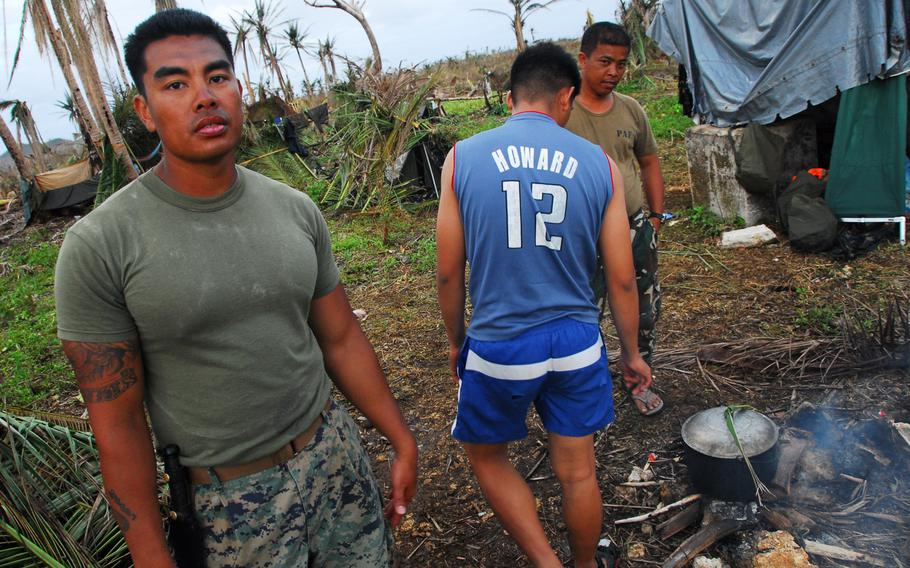 U.S. Marine Staff Sgt. John Suyat, 32, of Alexandria, Va., left, hung out with Filipino airmen while they cooked a local dinner on Thursday, Nov. 21, 2013, during typhoon relief operations in The Philippines.