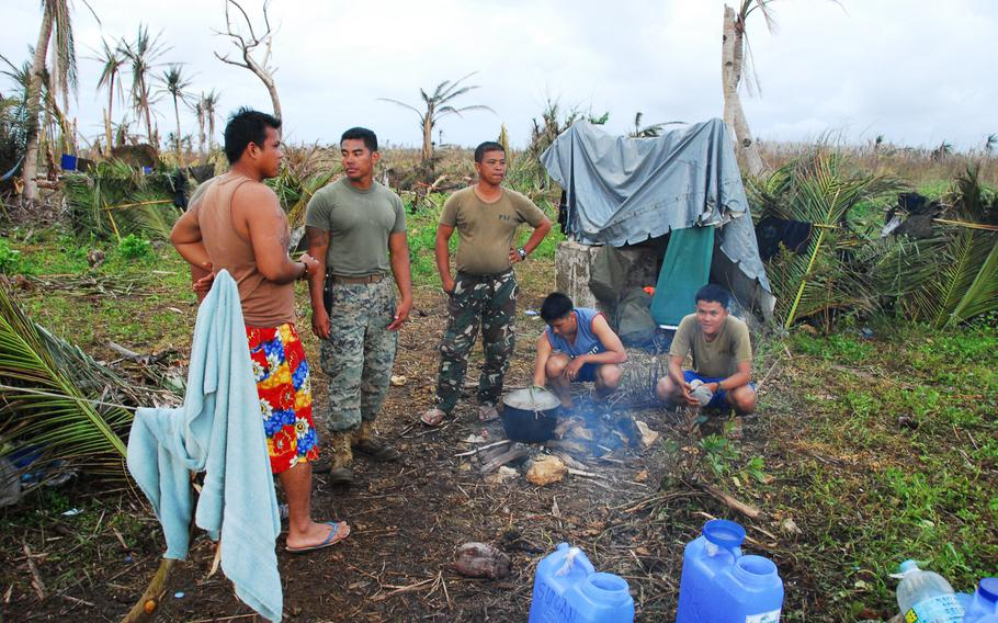 U.S. Marine Staff Sgt. John Suyat, 32, of Alexandria, Va., second from left, hung out with Filipino airmen while they cooked a local dinner on Thursday, Nov. 21, 2013, during typhoon relief operations in the Philippines.