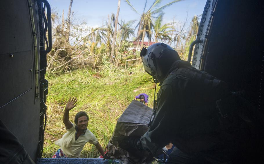 Petty Officer 3rd Class Peter Olson distributes supplies from an SH-60B Seahawk to citizens on Leyte in support of Operation Damayan in The Philippines on Nov. 16, 2013. The Seahawk is assigned to guided-missile cruiser USS Cowpens. Aboard Cowpens are several Philippine-born U.S. sailors helping with the post-typhoon aid effort.