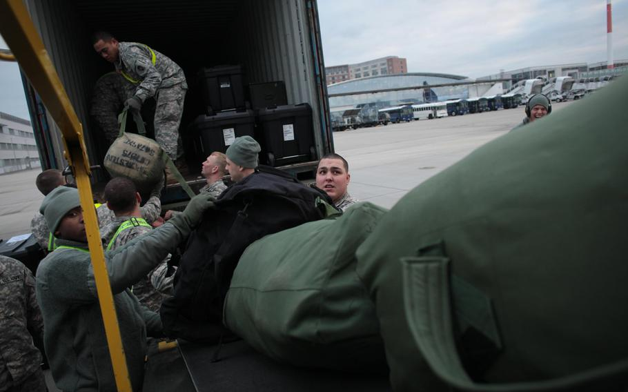 Soldiers of the 10th Army Air and Missile Defense Command load duffel bags and other military gear Monday, Dec. 2, 2013, onto a plane bound for Turkey. Soldiers of the unit's 5th Battalion, 7th Air Defense Artillery Regiment, will spend the next year defending Turkish airspace from missile and other aerial threats from neighboring Syria.