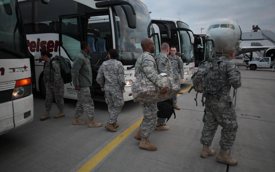 Soldiers of the 5th Battalion, 7th Air Defense Artillery Regiment, leave buses Monday, Dec. 2, 2013, and prepare to board a plane for Turkey, where they'll spend the next year defending Turkish airspace from missile and other aerial threats from neighboring Syria.