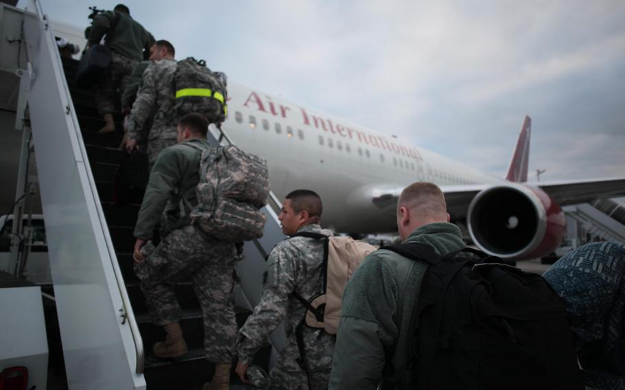 Soldiers of 5th Battalion, 7th Air Defense Artillery Regiment, board a plane Monday, Dec. 2, 2013, on their way to a yearlong deployment to Turkey.