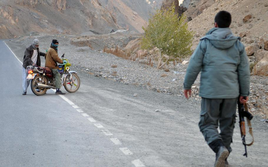 An Afghan National Police officer walks toward two motorists who failed to stop when he waved them down near the turn-off to Saighan district, a restive region of Bamiyan province, Afghanistan, where insurgent attacks are on the rise since international troops left in April.