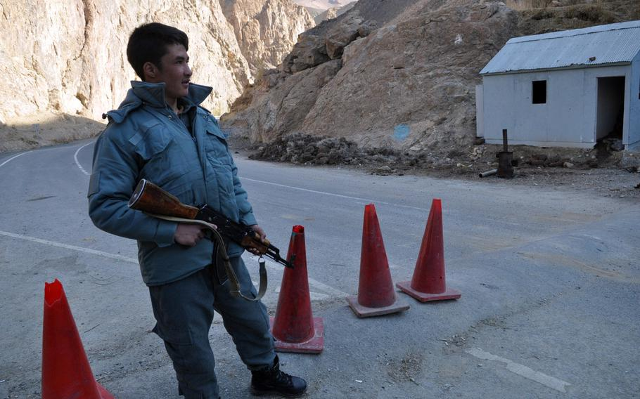 An Afghan National Police officer stands guard near the turn-off to Saighan district, a restive region of Bamyan province, Afghanistan, where insurgent attacks are on the uptick since international troops left in April.