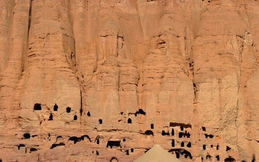 A man and two women walk by an ancient food storage building set hard against red cliffs that form the border of Bamiyan city, Afghanistan. Bamiyan is the capital of the province of the same name - one of the safest provinces in Afghanistan and also one of the poorest.