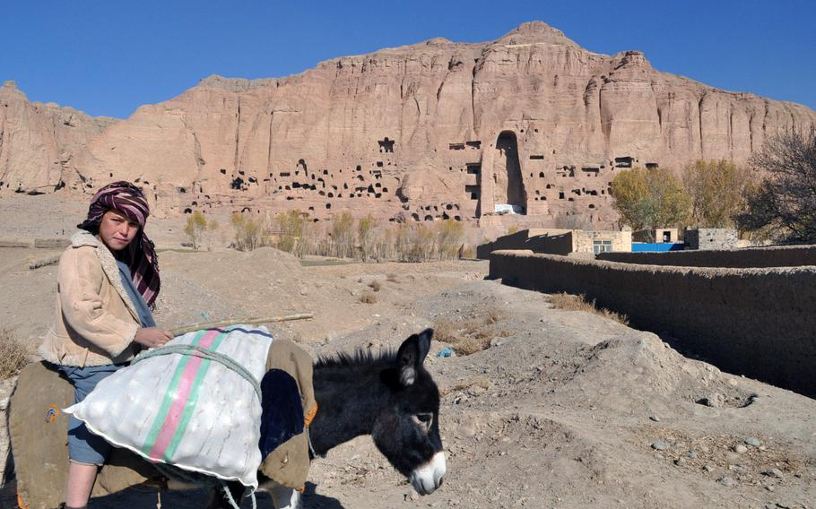 A young boy rides a donkey within view of the site of one of Bamiyan city's famed Buddhas. The giant Buddhas - representing a man, a woman, and a child - were infamously  blown up by the Taliban in 2001, but their dramatic outlines remain etched in sheer red cliffs at the edge of the city.