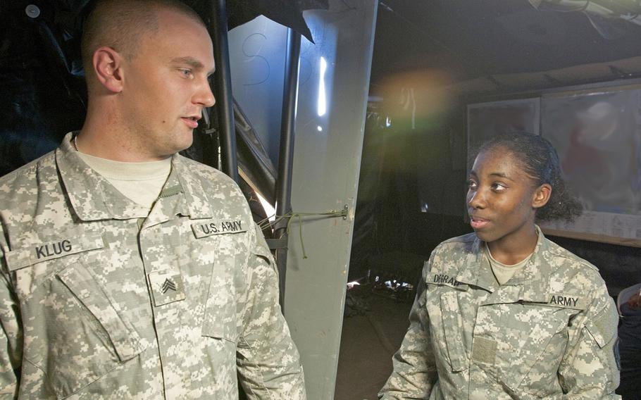 Pvt. Anika Degraff, a fire direction specialist with Headquarters and Headquarters Battery, 2nd Battalion, 20th Field Artillery Regiment, Task Force Pegasus Fires at Fort Hood, Texas, speaks with her supervisor Nov. 19 inside 2-20th FAR command tent during a validation exercise. Degraff is one of the first female fire direction specialists to assigned to 2-20th FAR.