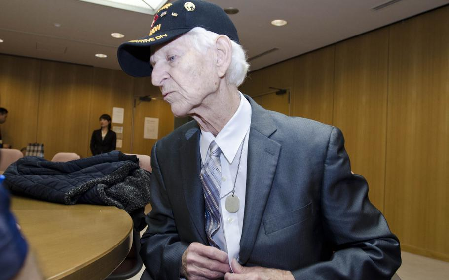 Kenneth Udstad, former Marine and World War II veteran, removes a flag that he took from the body of a deceased soldier from inside his shirt Dec. 6, 2013, in Shizuoka, Japan. ???If you want to know where I found the flag??? this is where the Jap was carrying it,??? Udstad said.
