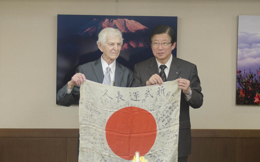 Kenneth Udstad, former Marine and World War II veteran, meets with Japanese officials in Shizuoka, Japan, to return a flag and other items he recovered from dead soldiers during WWII.