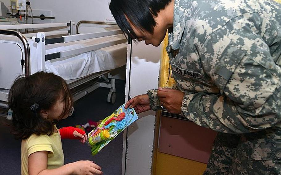 First Sergeant Takisha Benitez hands a gift to a patient at the Children?s Cancer Clinic at the University of Mainz Medical Center Dec. 11, 2013. Fourteen soldiers from the U.S. Army Garrison Wiesbaden?s Better Opportunities for Single Soldiers handed out toys and cards to children at the clinic.