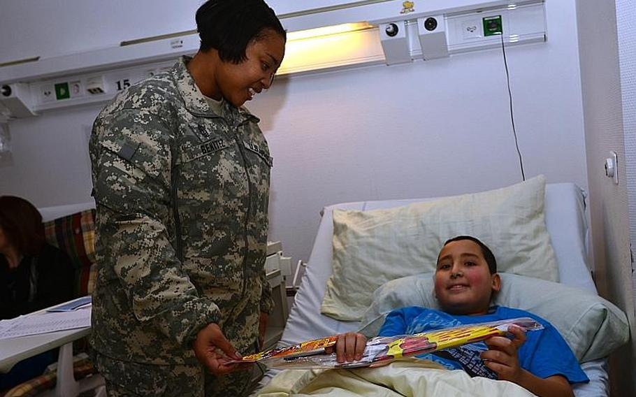 First Sergeant Takisha Benitez hands a gift to a patient at the Children?s Cancer Clinic at the University of Mainz Medical Center Dec.11, 2013.  Fourteen soldiers from the U.S. Army Garrison Wiesbaden?s Better Opportunities for Single Soldiers handed out toys and cards to children at the clinic.