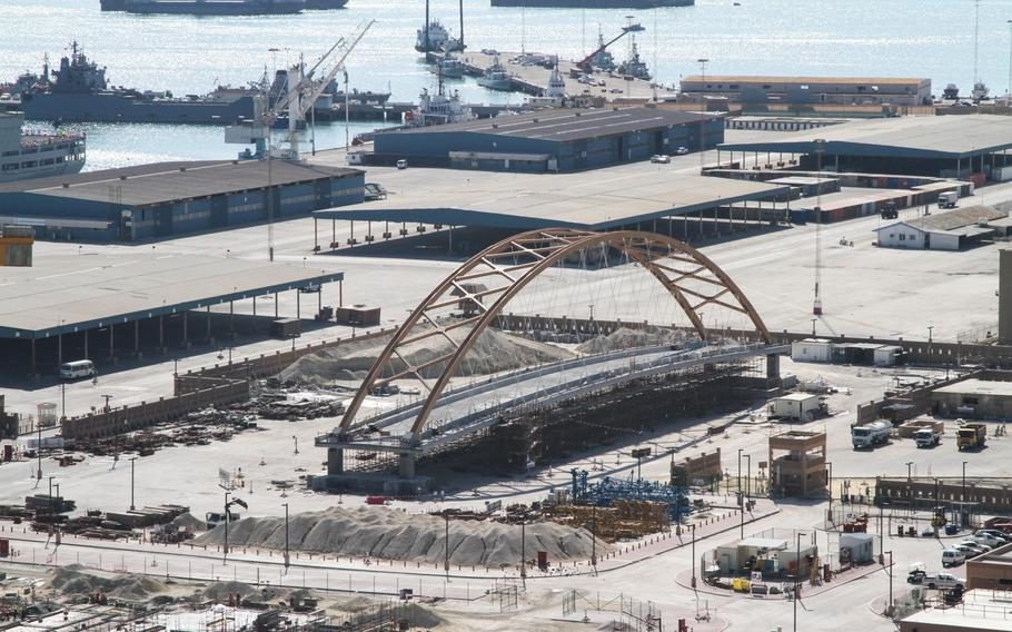 A tied-arch suspension bridge is being assembled across from Naval Support Activity Bahrain, Dec. 5, 2013. Next month the 2,500-ton bridge is scheduled to be lifted and moved into position over the roadway connecting the base to 77 acres of land the Navy leases along the waterfront.