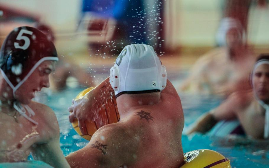 In game one of the Warrior Transition Battalion — Europe's water polo tournament, Spc. James Viloria of the battalion's Company A, spins and tries to score with a backhand throw against the defenders of Company B Thursday, Dec.12, 2013.