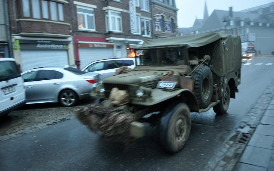 Re-enactors drive a restored U.S. Army military vehicle through downtown Bastogne, Belgium on Dec. 14, 2013, in preparation for events commemorating the Battle of the Bulge during World War II.