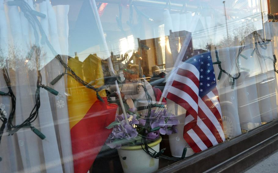Belgian and American flags sit in the window of a cafe in Bastogne, Belgium. The town hosted thousands of re-enactors and spectators for a walk, a parade, and wreath laying to commemorate the siege of the town by German forces in World War II.