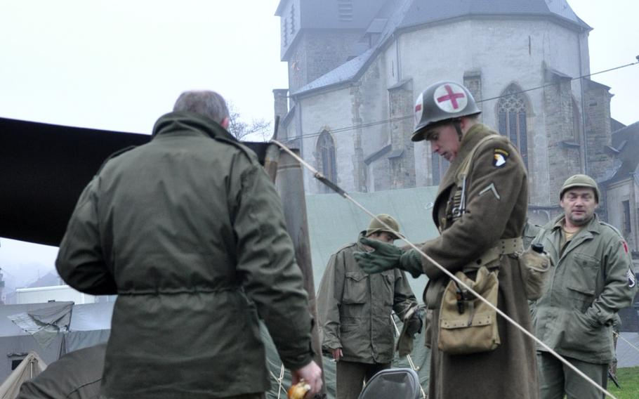 Re-enactors near St. Peter's church prepare for a day of remembering the Allied defense of the town of Bastogne, Belgium during World War II.