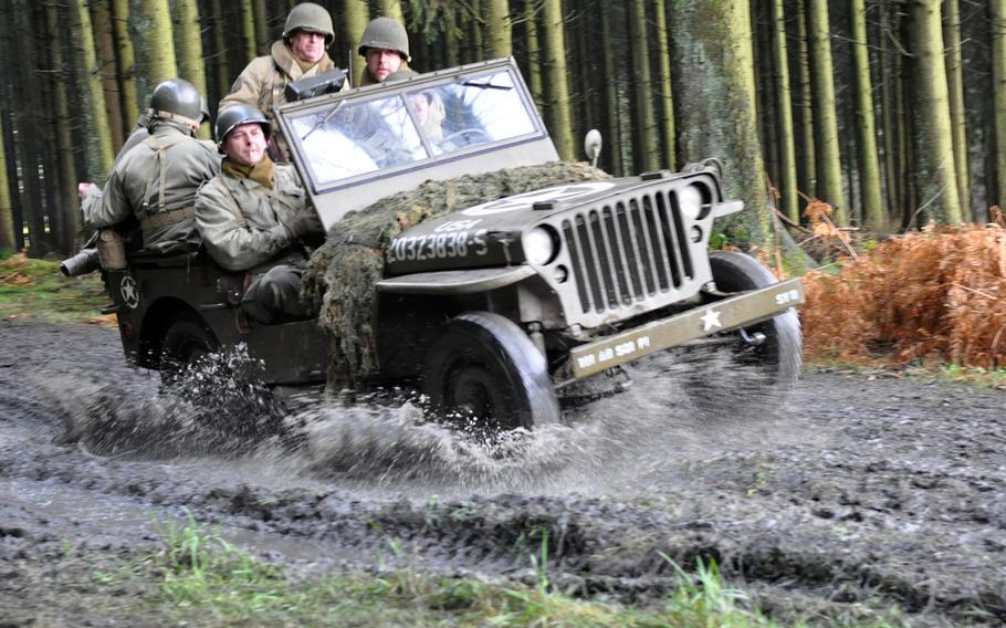 Re-enactors dressed in period uniforms drive a jeep through mud and water during an event to commemorate the Battle of the Bulge in World War II. The event, held Dec. 14, 2013, in Bastogne, Belgium, brought in participants and re-enactors from around the United States and Europe.