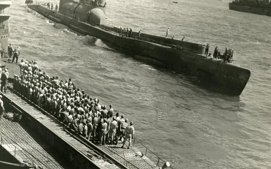 U.S. Navy sailors watch the I-400 roll past in Japanese waters at the end of World War II.