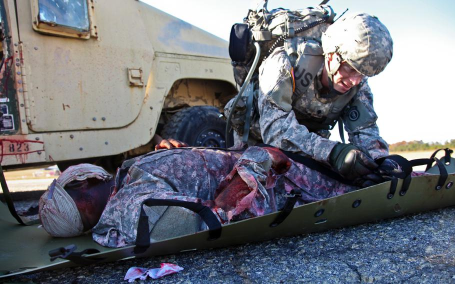 Spc. Adam T. Christensen tightens a  wounded soldier down so he does not fall out during the Best Warrior Competition at Fort Lee. Virginia, on Nov 19, 2013. The straps need to be tight so the soldier does not sustain any more injuries.