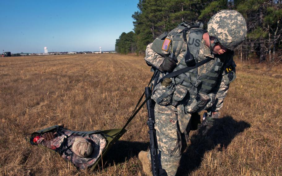 Spc. Adam T. Christensen drags a wounded soldier to the landing zone during enemy fire for the Best Warrior Competition at Fort Lee. Va., on Nov 19, 2013. This training exercise is meant to push the candidates to their limit.