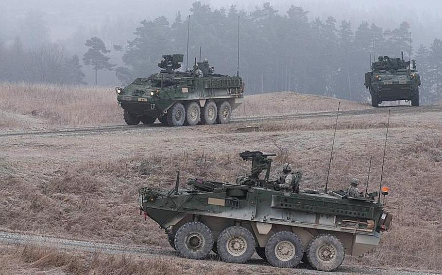 Stryker armored combat vehicles patrol USAG Bavaria's new convoy live-fire course during its opening, Dec. 18, 2013.