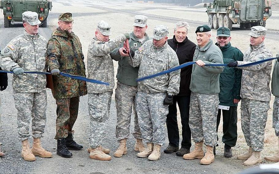 Joint Multinational Training Command officials, including Commander Brig. Gen. Walter E. Piatt and Command Sgt. Maj. Jeffery R. Huggins, cut the ceremonial ribbon during the opening of USAG Bavaria's new convoy live-fire course, Dec 18, 2013.