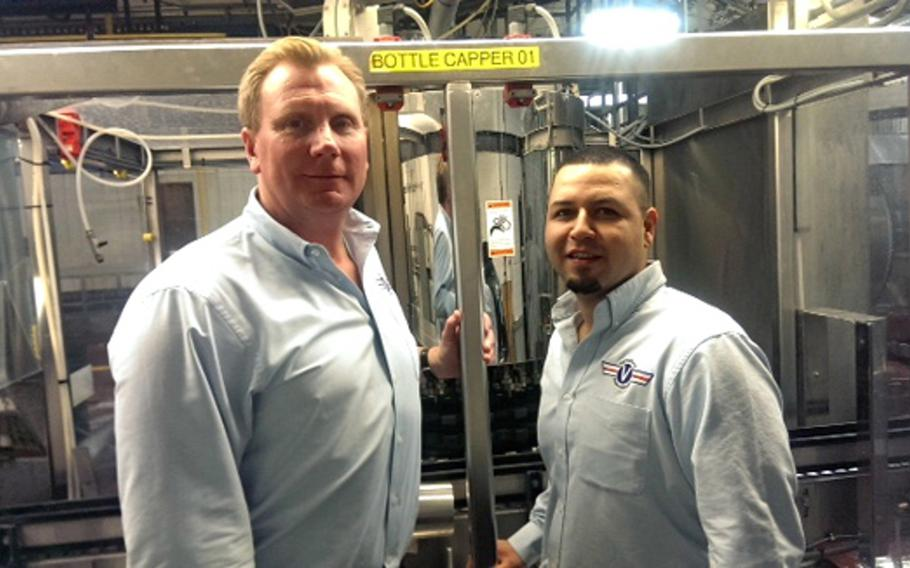 Veteran Beer Company CEO Paul Jenkins, left, and brand ambassador Miguel Delgado pose for a photo in front of their Cold Spring, Minn., facility's bottle capper.