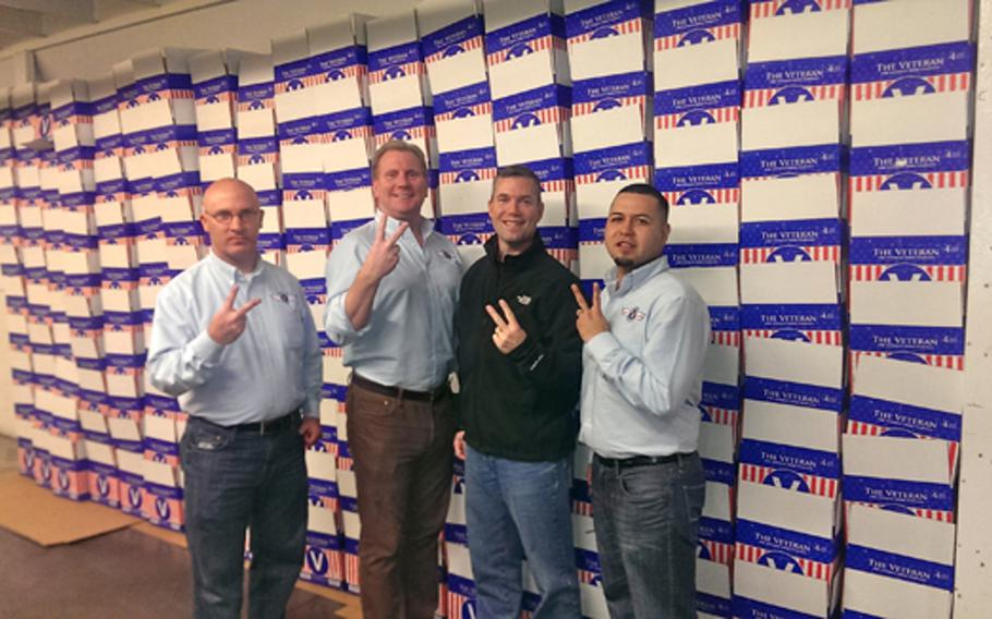 """From left, Marc Blue, Veteran Beer Company director for Illinois, CEO Paul Jenkins, brewer Eric Rine and brand ambassador Miguel Delgado flash the Veteran """"V"""" at their Minnesota facility."""