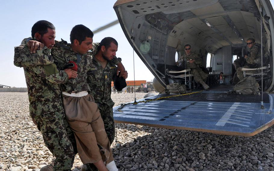Two Afghan National Army soldiers help a wounded comrade into the back of an Afghan Air Force Mi-17 helicopter at Camp Leatherneck in southwest Afghanistan, June 18, 2013.