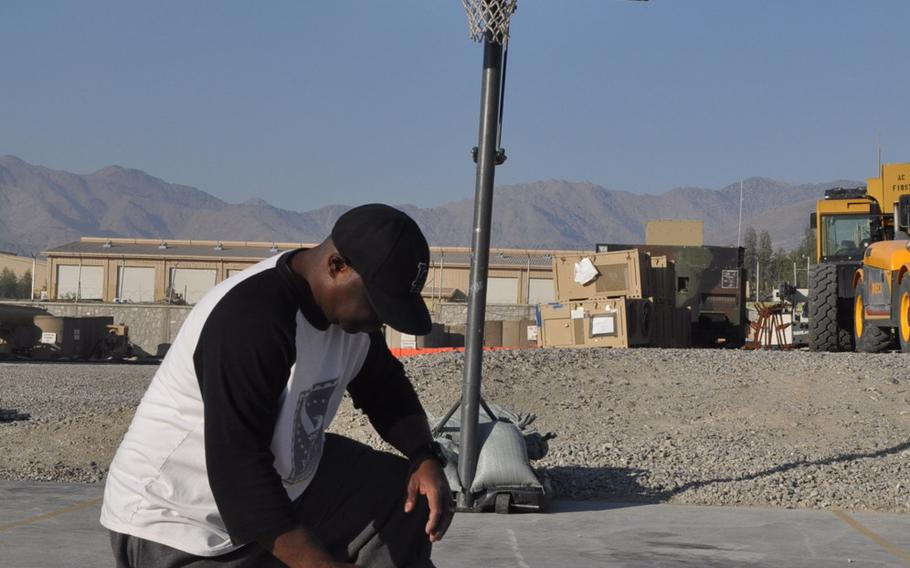 Daryll Packer, a military contractor and certified basketball referee, measures the court for a Christmas Day five-on-five game at Forward Operating Base Gamber in Afghanistan. The court is next to the FOB's helicopter landing zone, amid the rugged mountains that cover most of the eastern part of the country.