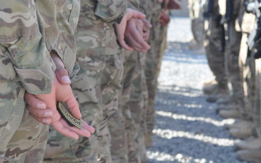 On Forward Operating Base Gamberi in Afghanistan's Laghman province, two units received 10th Mountain Division combat patches on Christmas Eve. Here, soldiers hold the patches while at parade rest before a patch ceremony.