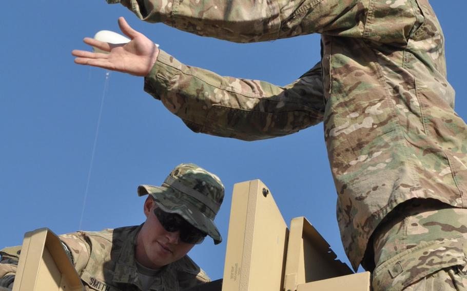 Sgt. Donavin Smith, left, and Spc. Erik McEowen clean the turret of a mine-resistant ambush-protected vehicle on Christmas Eve. While many soldiers get a break on Christmas Day, work on Dec. 24 continued pretty much as usual on Forward Operating Base Gamberi in Afghanistan's Laghman province.