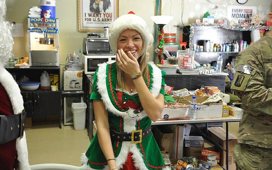 USO Programs Coordinator Heather Oliver broke into laughter as the USO staff prepared to welcome soldiers in for a holiday party. Soldiers were invited to watch Home Alone, stuff themselves with fudge and cookies and take pictures with Frosty the Snowman, Santa and his elves.