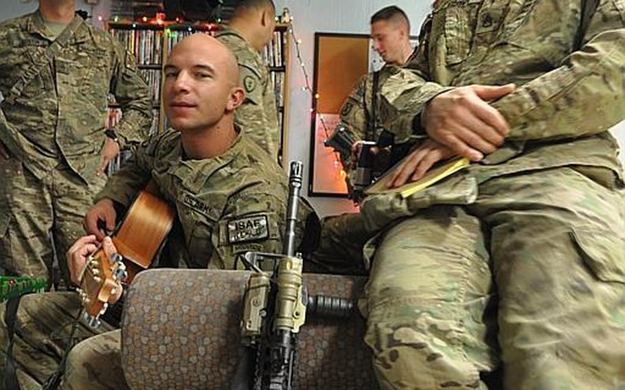 A soldier strums a guitar during a USO holiday party at Forward Operating Base Fenty. The party went on for 12 hours so people could wander in between shifts. Many soldiers and civilians still worked and went out on missions on Dec. 25, despite the holiday.
