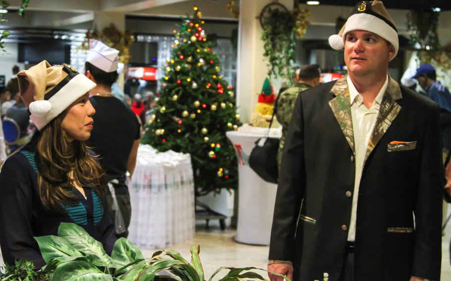 Chief Petty Officers Marina Chavez and Jeremy Gatewood oversee volunteers and direct traffic at a special Christmas Day buffet prepared by Navy Morale, Welfare and Recreation at the U.S. Navy base in Bahrain.