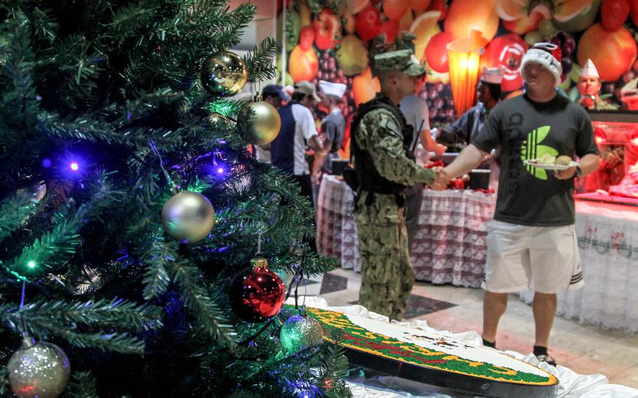 Petty Officer 3rd Class Cody Willis, left, and Seaman Matthew Vaughn wish each other a Merry Christmas at a meal for servicemembers at the U.S. Navy base in Bahrain.