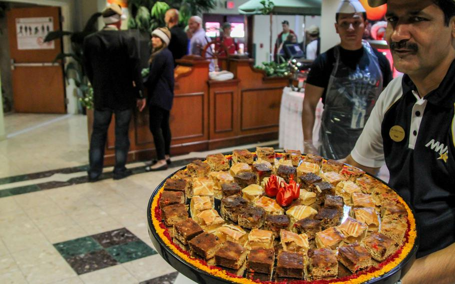 A Navy Morale, Welfare and Recreation food worker brings out sweets at a Christmas Day meal for servicemembers at the U.S. Navy base in Bahrain.