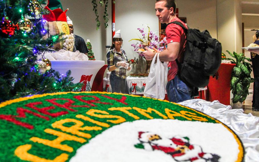 Seaman Sean Pearson from the aircraft carrier USS Harry S. Truman finds a table at a Christmas buffet prepared by Navy Morale, Welfare and Recreation at the U.S. Navy base in Bahrain. The Truman is on five-day port visit to Bahrain.