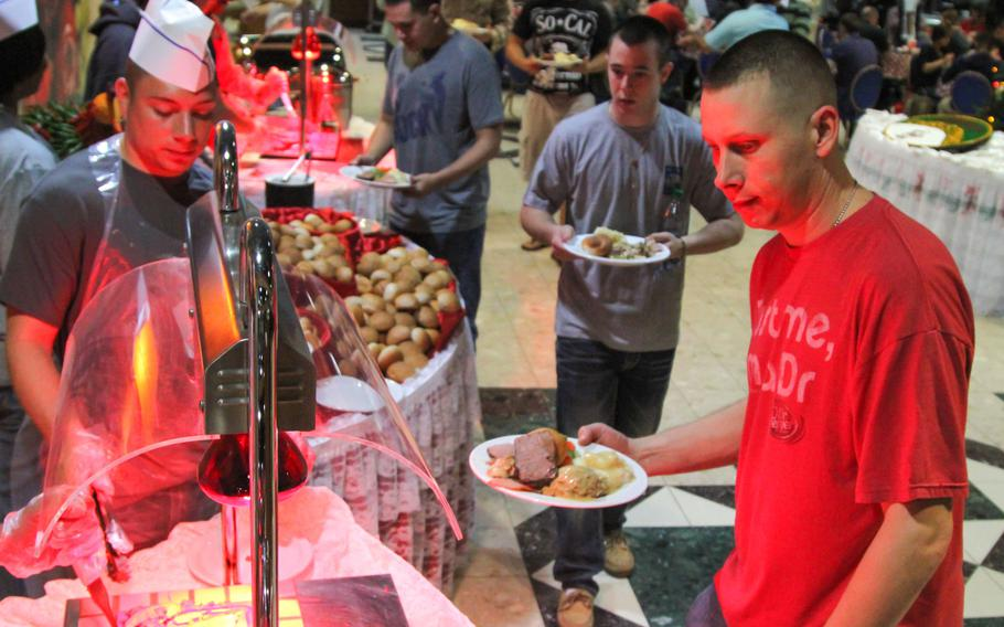 Servicemembers wend their way through the line at a Christmas buffet prepared by Navy Morale, Welfare and Recreation at the U.S. Navy base in Bahrain.